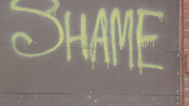 """Ordet """"shame"""" på en husvägg"""