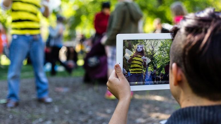 Pojke med Ipad fotar en man utklädd till ett bi