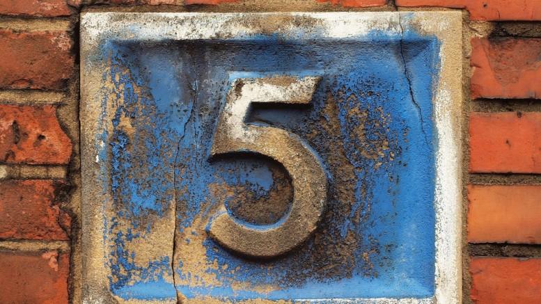Siffran fem på en husvägg