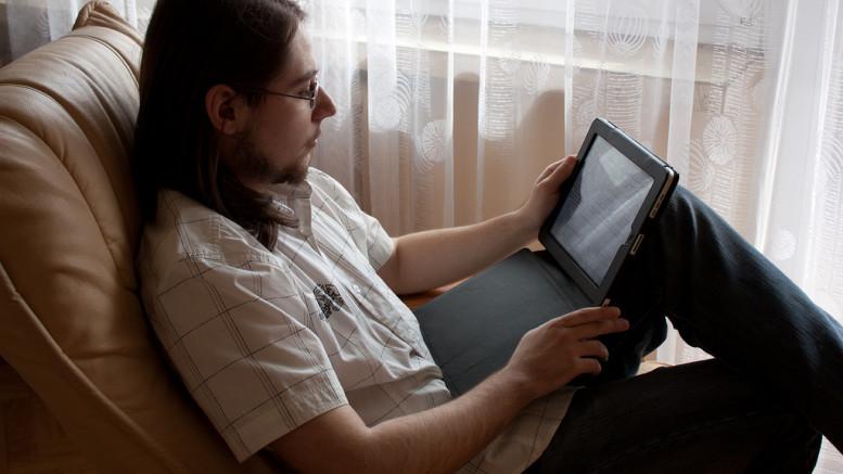 Man som läser på en iPad