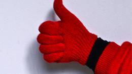 En hand med röd vante som gör tummen upp
