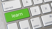 """Ett tangentbord med en tangent märkt """"learn"""""""