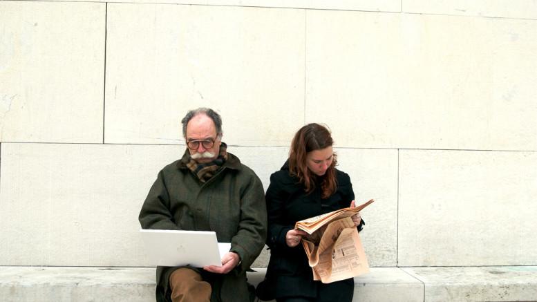 Två människor på en bänk läser. Den ena från en dator. Den andra från en tidning.