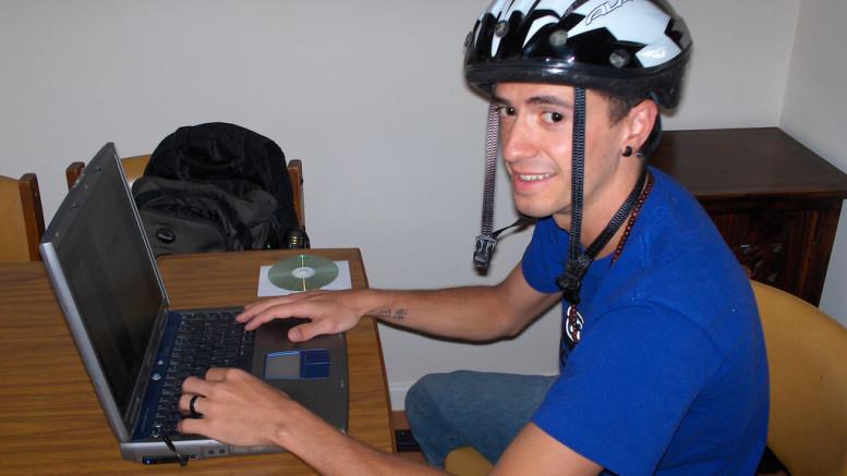 En man som surfar på internet iklädd cykelhjälm